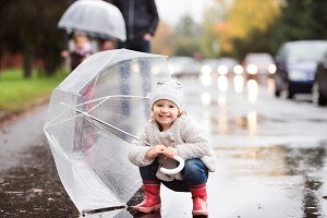 Little girl under the umbrella. Walk on rainy day.