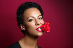 beautiful woman with rose in mouth