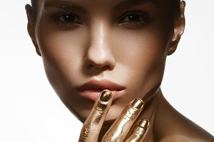 girl with golden paint on fingers