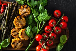 grilled vegetables on a wooden tray on a black slate. copy space