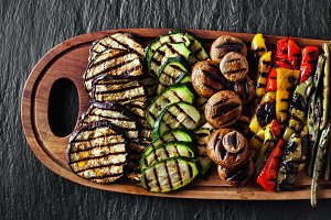 a large wooden tray with a Summer snack, colorful Barbecue Veget