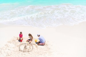 Family making sand castle at tropical white beach.