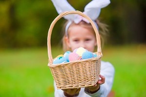 Adorable little girl wearing bunny ears with a basket full of Easter eggs on spring day outdoors