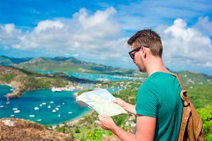 Young tourist man with map background of English Harbor from Shirley Heights, Antigua, paradise bay at tropical island in the Caribbean Sea