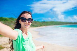 Young woman taking selfie portrait background turquiose ocean