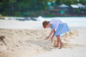 Adorable little girl at white beach during summer vacation
