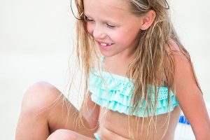 Little girl having fun at tropical beach playing on sunbed