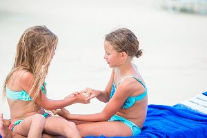 Little girls having fun at tropical beach playing together on sunbed