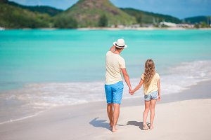 Adorable girl and young father at tropical beach