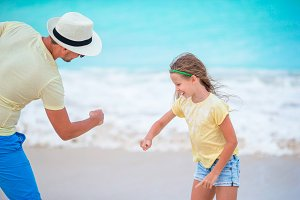 Happy father and his adorable little kid at tropical beach having fun together