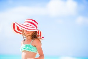 Adorable little girl in big hat on white beach