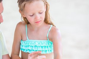 Careful father applying sun cream to kid nose. Portrait of lttle girl in suncream