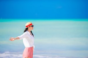 Young woman enjoying the sun sunbathing by perfect turquoise ocean.