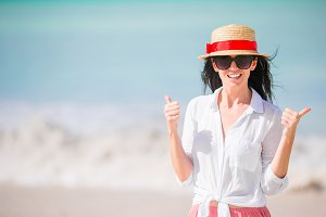 Young woman enjoying the sun sunbathing by perfect turquoise ocean. Girl lifts thumbs up outdoors