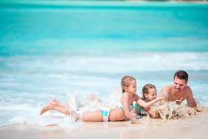 Father and little kids enjoying beach summer tropical vacation playing in shallow water