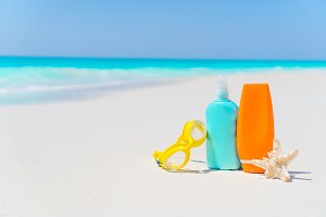 Suncream bottles, glasses, starfish on white sand beach