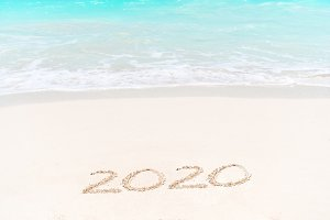 2020 handwritten on sandy beach with soft ocean wave on background