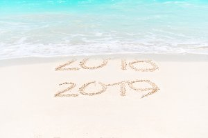 2018 and 2019 handwritten on sandy beach with soft ocean wave on background