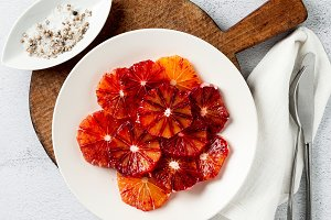 sliced red orange slices on a plate. base for dessert or salad.