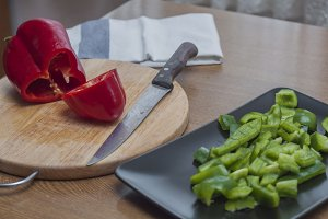 Sliced green and red peppers on wood