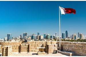 Bahrain Flag with skyline of Manama at Bahrain Fort. A UNESCO World Heritage Site