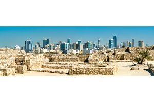 Ruins of Bahrain Fort with skyline of Manama. A UNESCO World Heritage Site