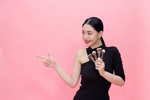 Young Stylish Asian woman carrying makeup brushes on hand with copy space. Beautiful fashionable woman isolated over pink background. makeup product presentation concept