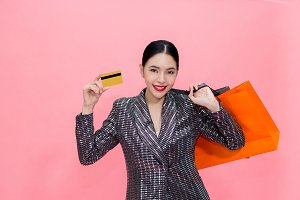 Young Stylish Asian woman carrying shopping bags and holding credit card. Beautiful fashionable woman isolated over pink background. Shopping and Finance concept