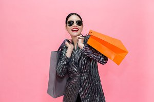 Young Stylish Asian woman carrying shopping bags and holding credit card. Beautiful fashionable woman with sunglasses isolated over pink background. Shopping and Finance concept