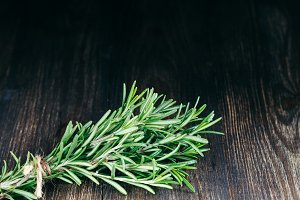 Organic bunch of fresh rosemary on wooden table