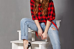 Girl in a hat, plaid shirt and jeans