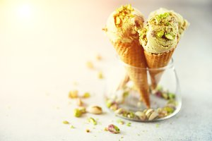 Green ice cream in waffle cone with chocolate and pistachio nuts on grey stone background. Summer food concept, copy space. Healthy gluten free ice-cream. Banner