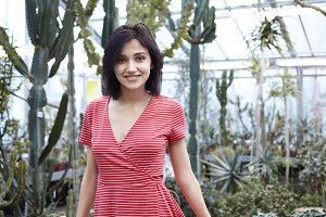 Vertical portrait of attractive young Caucasian female with cute smile posing in spacious greenhouse with big cacti and succulent plants in background, wearing beautiful red dress with white stripes