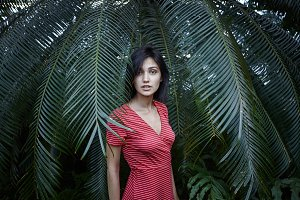 Portrait of fashionable bob-haired pretty girl wearing red and white striped dress standing at palm tree among its huge leaves and looking at camera with lips parted. Nature and beauty concept