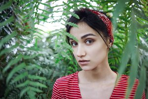 Beauty, style, fashion, spa and skincare concept. Fashionable young lady with red headband posing among exotic green plants for herbal cream and organic cosmetic products, having serious look