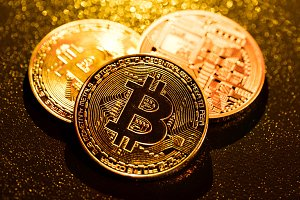 Three golden bitcoin coins on black