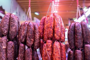 Sausages hanging on string on market stall