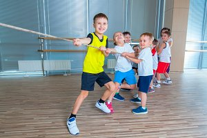 Children and recreation, group of happy multiethnic school kids playing tug-of-war with rope in gym