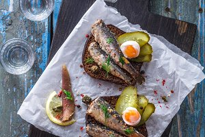 Vodka and a set of sandwiches with sprats on a wooden background. Top view. Copy space