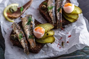 Sandwich with sprats and egg on wooden table, close up