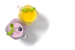 Purple and yellow smothies with mint in mason jar glass with berries and mint. Above view on white table. Healthy food.