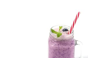 Blueberry smoothie with mint in mason jar glass with berries and mint. Above view on blue table. Healthy food.