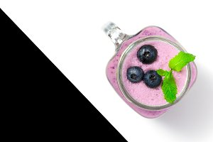 Blueberry smoothie with mint in mason jar glass with berries and mint. Above view on white and black table. Healthy food.