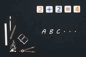 School supplies placed on black background with text ABC