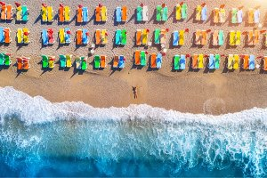 Aerial view of lying woman on the beach with colorful chaise-lou