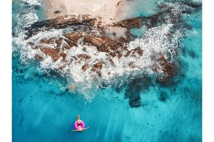 Aerial view of woman swimming on the pink swim ring in the trans