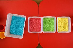 Sensory bin for toddlers with colourful rice on red table. Universal educational game