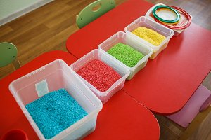 Sensory bin for toddlers with colourful rice on red table.
