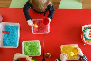Toddlers playing with sensory bin with colourful rice on red table. Top view