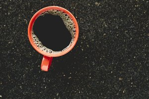 Cup of coffee on granite table, top view